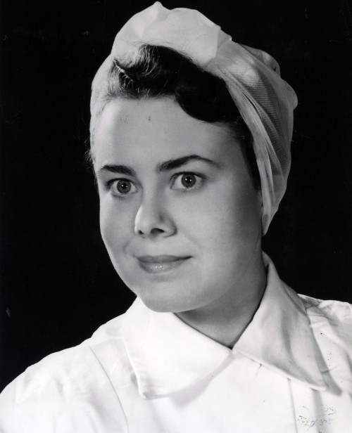 SA/BR/10/IMA/2/1 - Photograph of female shop employee June Woolley in 1950s uniform