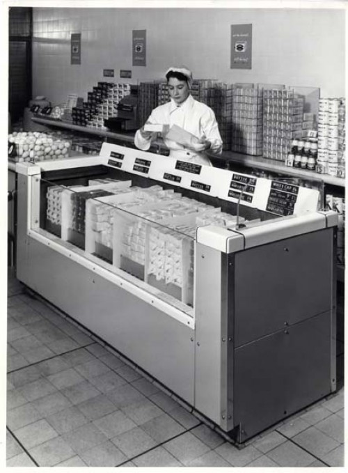 SA/BR/16/IMA/1/1 - Photograph of shop counter with female employee and refrigerated cabinet containing dairy products