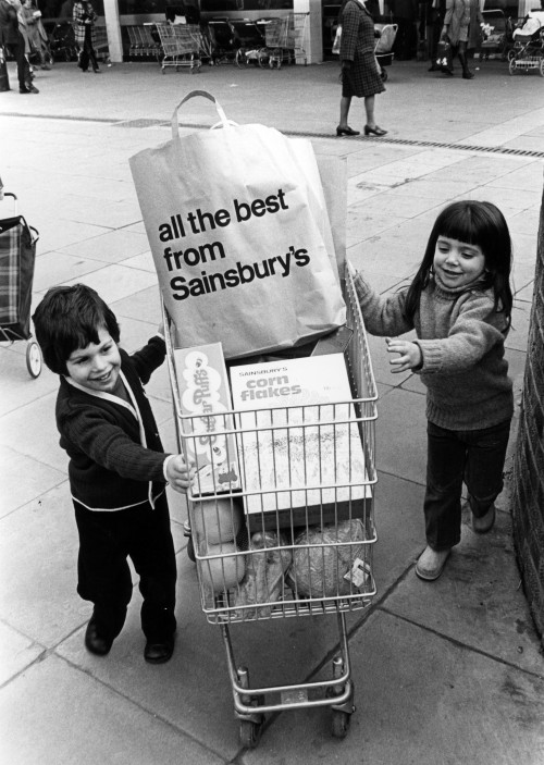 SA/BRA/5/11/8 - Photograph of children pushing trolley with 'all the best from Sainsbury's' bag inside