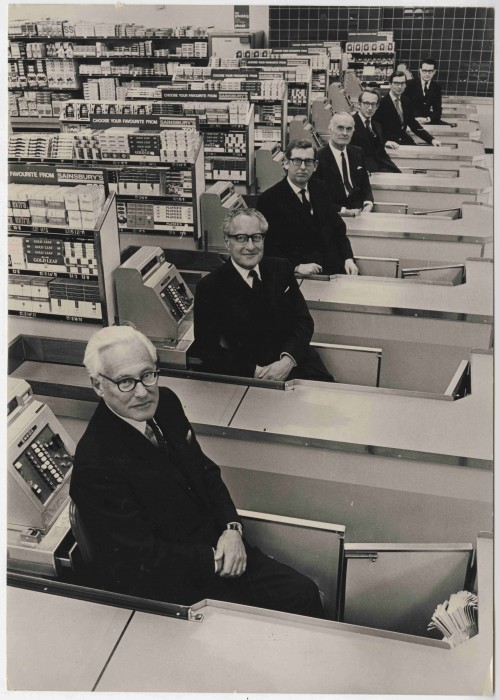 SA/FAM/10/2/1 - Photograph of seven Sainsbury family members at checkouts of a store