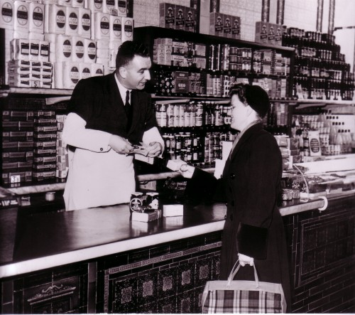 SA/WAR/2/IMA/1/9 - Photograph of customer being served at counter, with coupons being cut from her ration book
