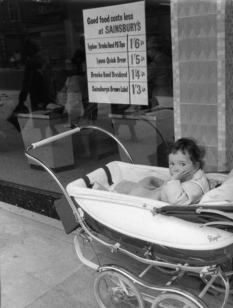 SA/BRA/5/11/1 - Photograph of baby in pram outside Sainsbury's store