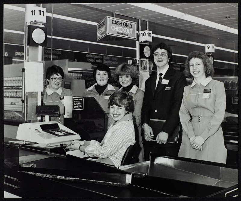 SA/BRA/7/B/19/2 - Image of Mark Smith (Checkout Manager) and colleagues at the checkout area of Woodchurch Road, Birkenhead branch