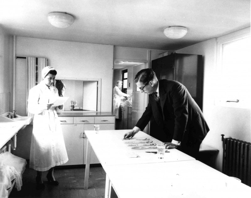SA/FAM/5/IMA/2/1 - Photograph of JD Sainsbury with woman carrying out bacon quality control, 1957