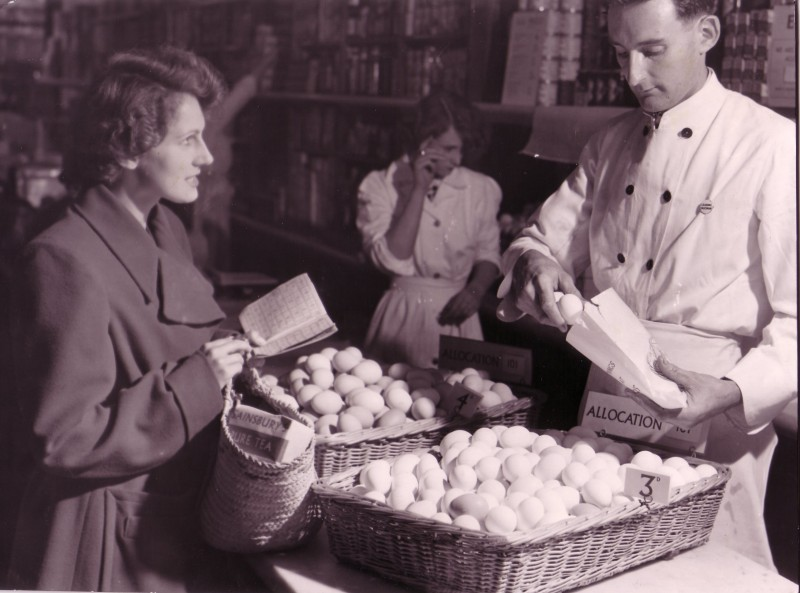 SA/WAR/2/IMA/1/8 - Photograph of customer with ration book being served with eggs